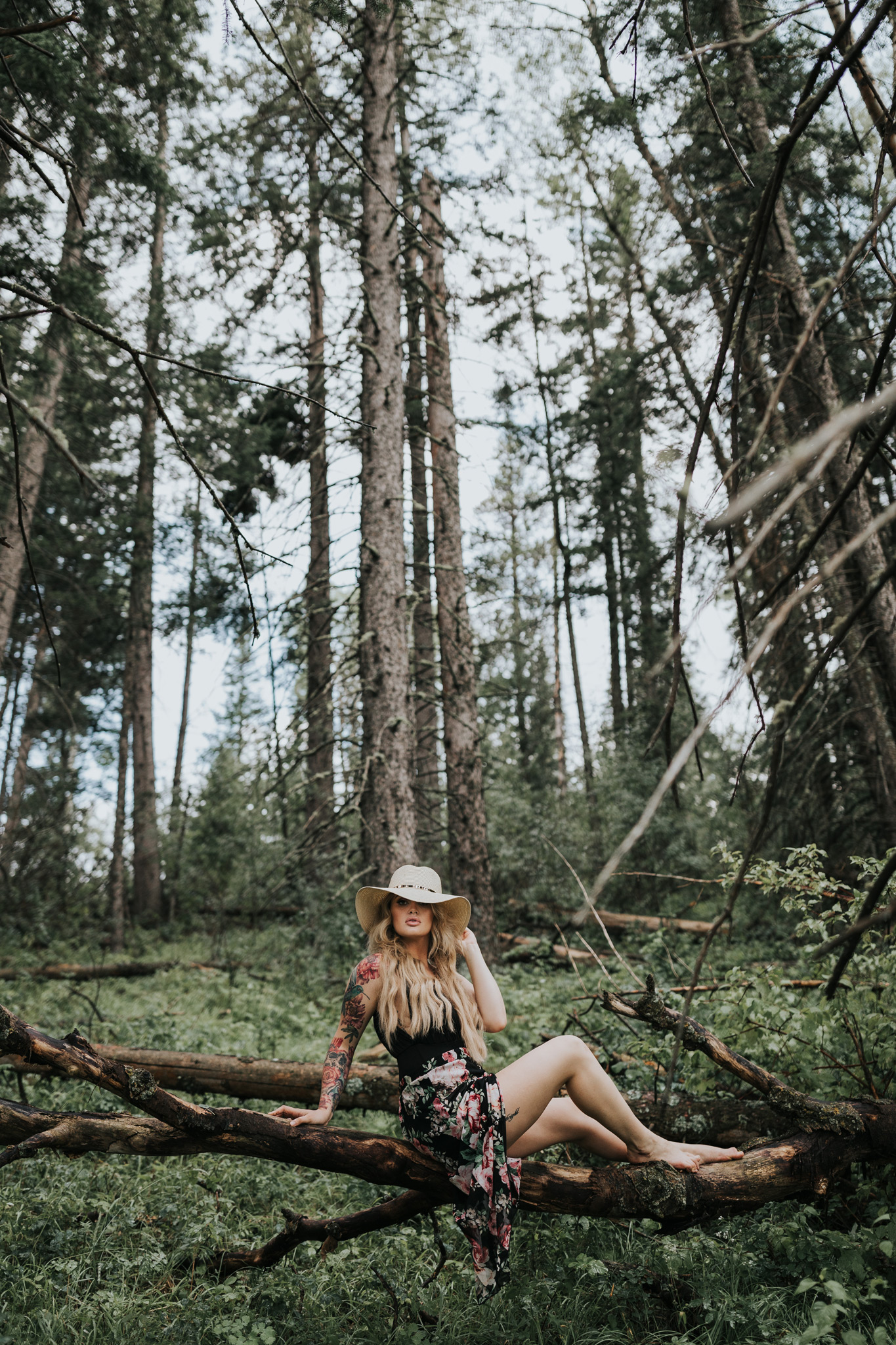 woman sitting on suspended tree log touching hat brim cypress hills