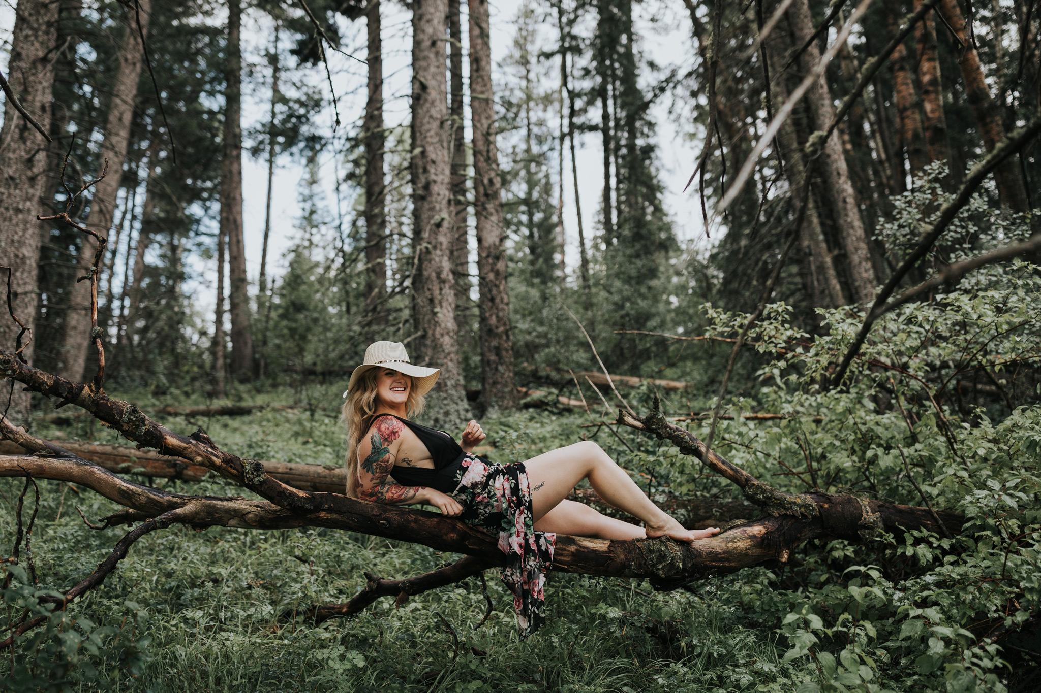 woman lounging on suspended tree log laughing elkwater alberta
