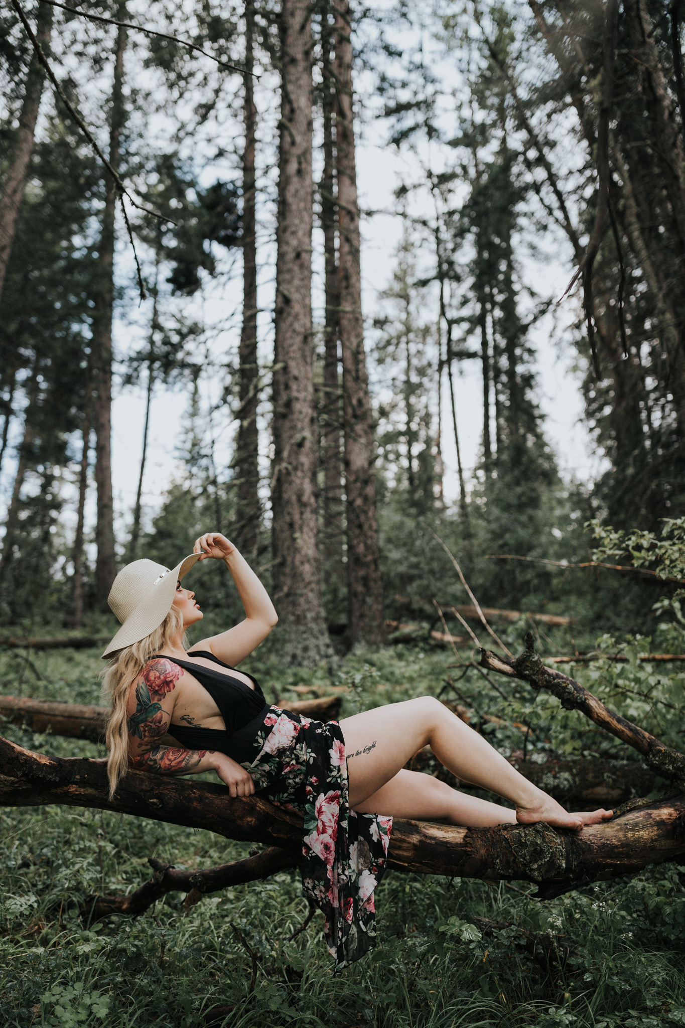 woman lounging on suspended tree log in forest wearing floppy hat