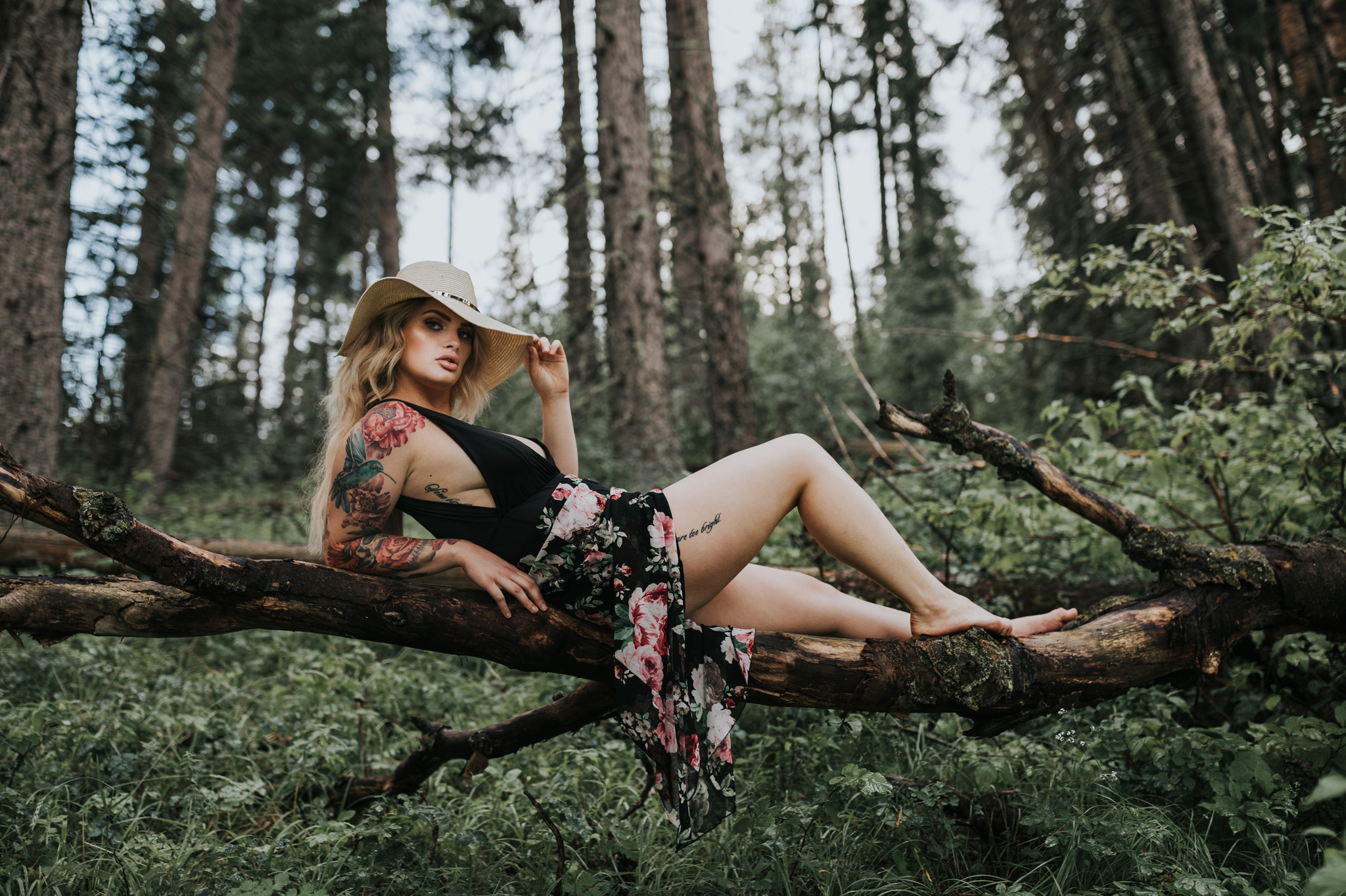 woman lounging on tree log in cypress hills forest holding brim of her hat portrait