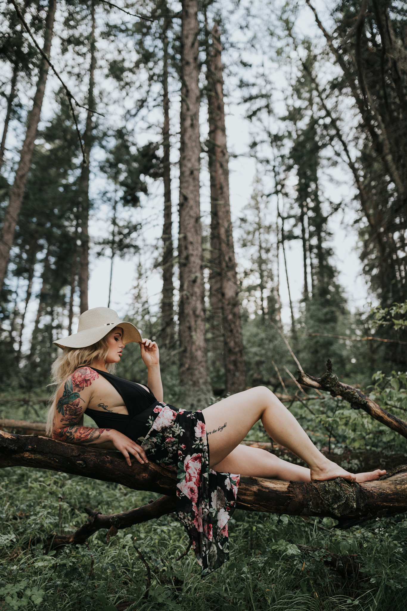 woman lounging on tree log in reesor lake forest holding brim of her hat