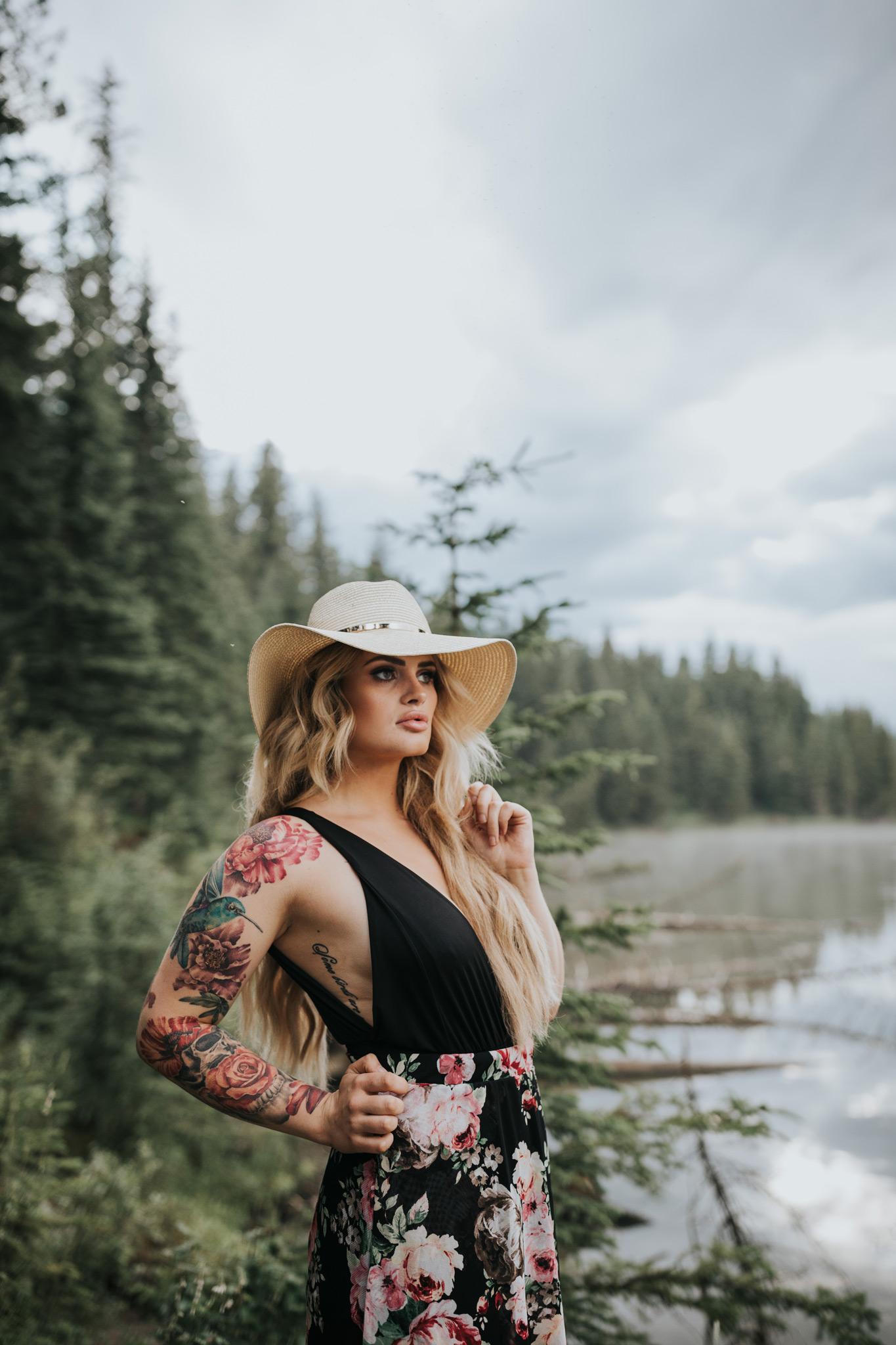 woman standing by reesor lake alberta wearing floppy hat