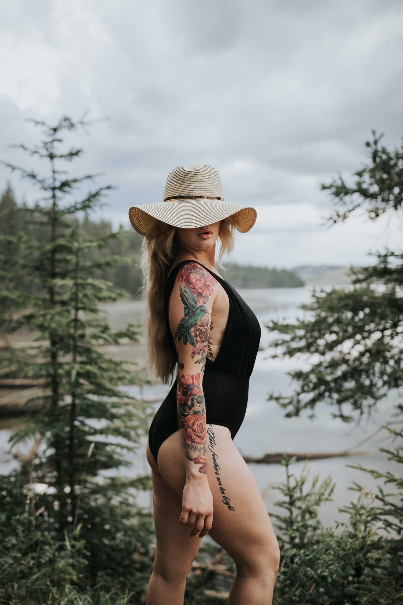 woman posing by reesor lake wearing floppy hat covering eyes