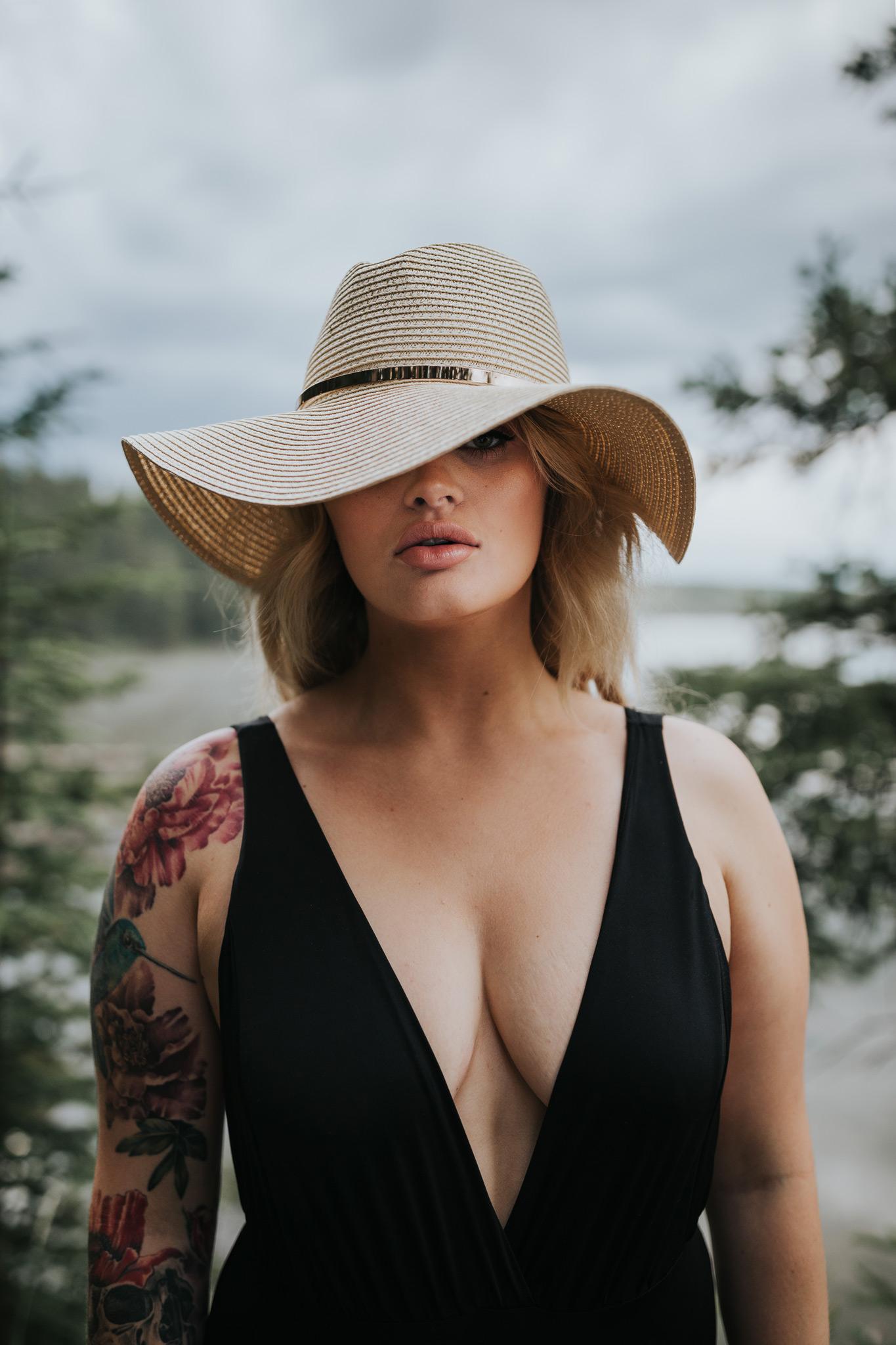 portrait of woman by reesor lake wearing floppy hat covering one eye