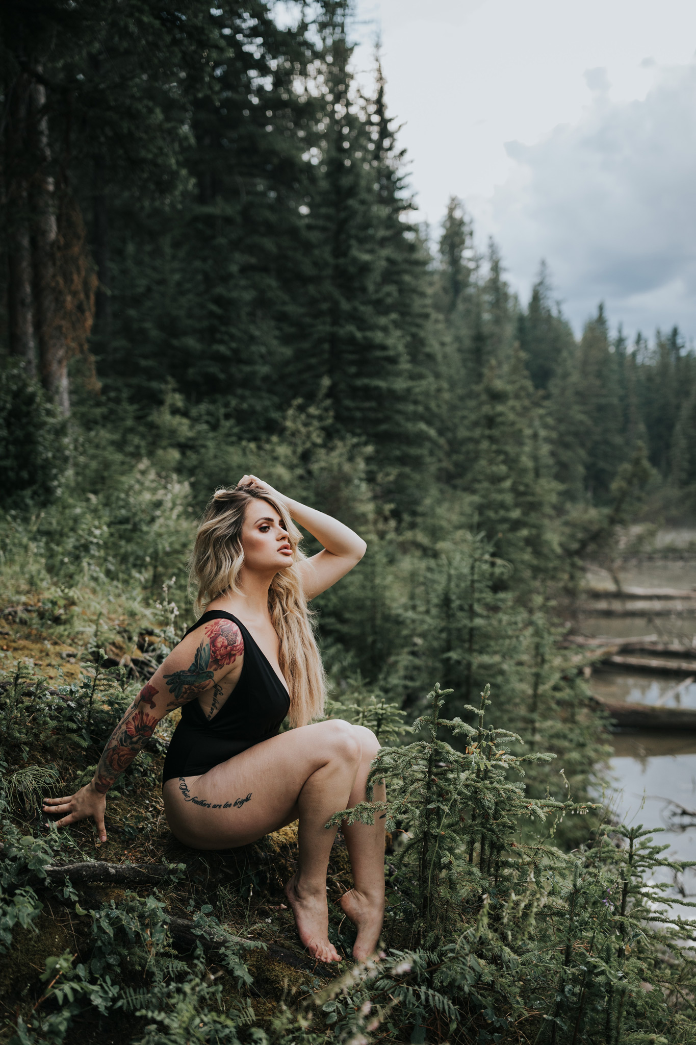 woman sitting barefoot in forest by reesor lake alberta