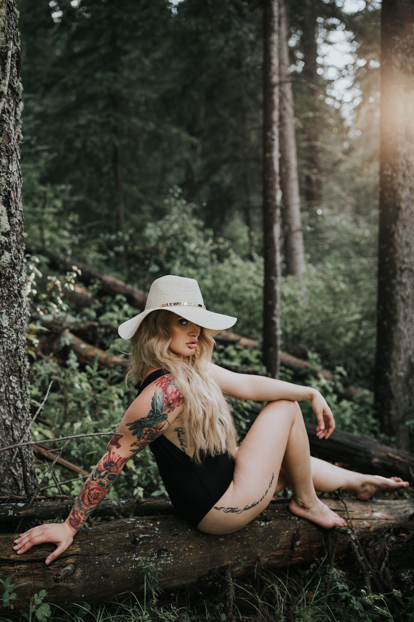 woman sitting on fallen tree log in cypress hills forest
