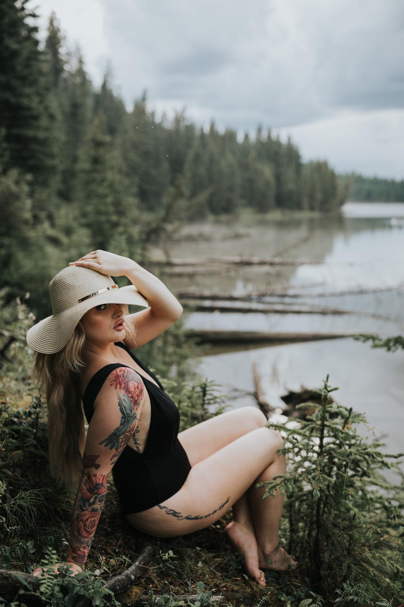 woman sitting holding hat on head by reesor lake alberta