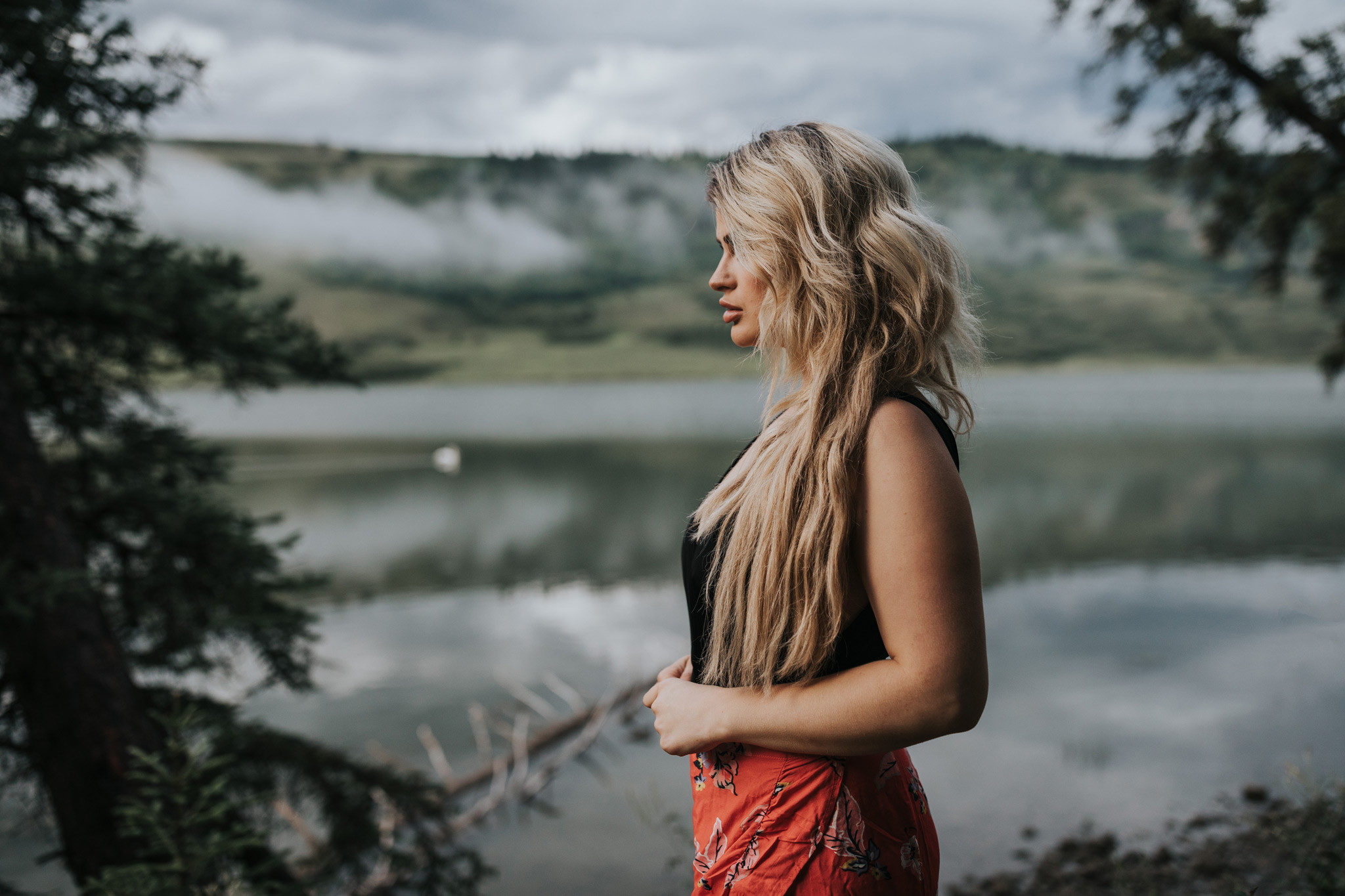woman standing in front of cloudy lake view