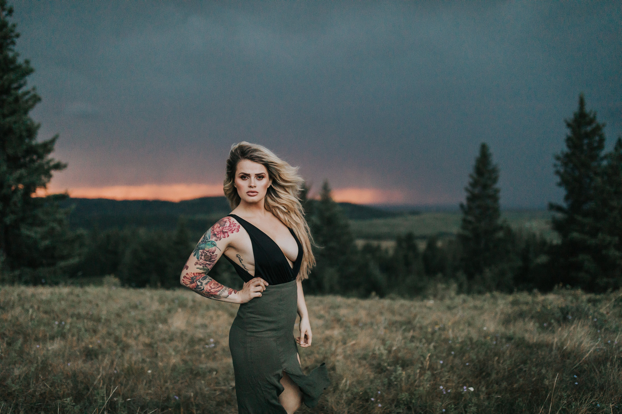 woman posing at stormy alberta sunset hair blowing
