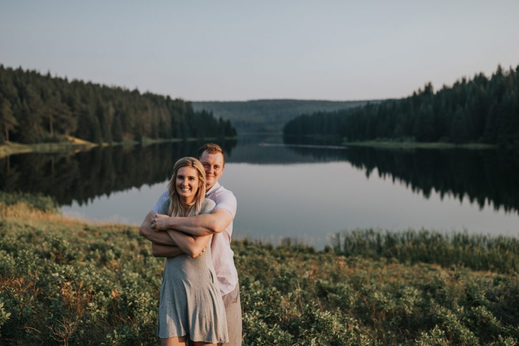 man hugging fiancé from behind at spruce coulee campground