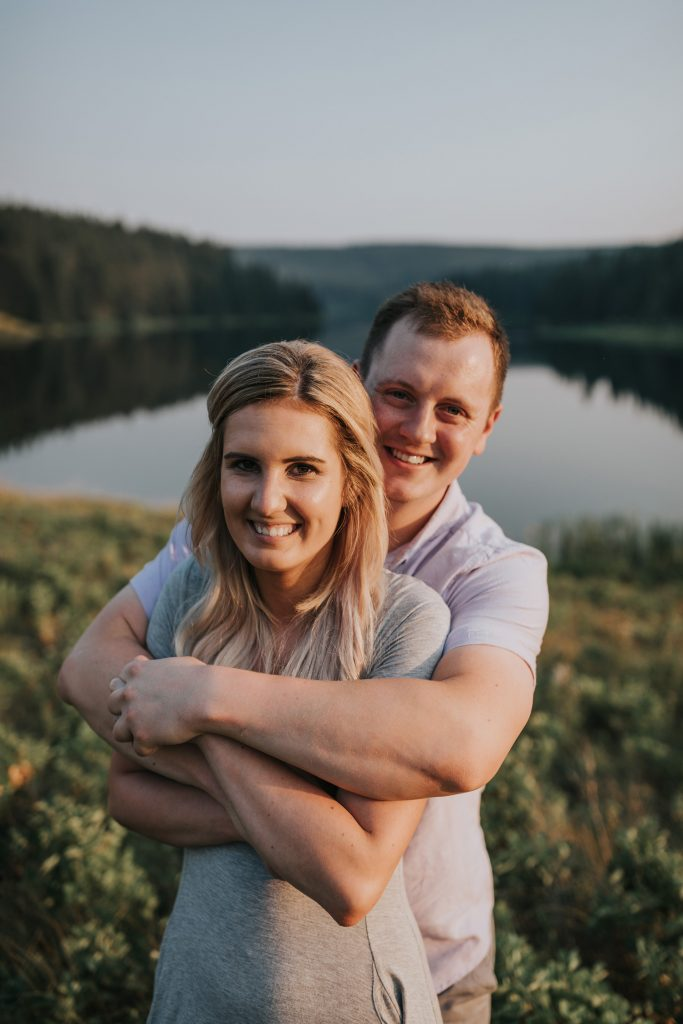 couple smiles with arms intertwined alberta
