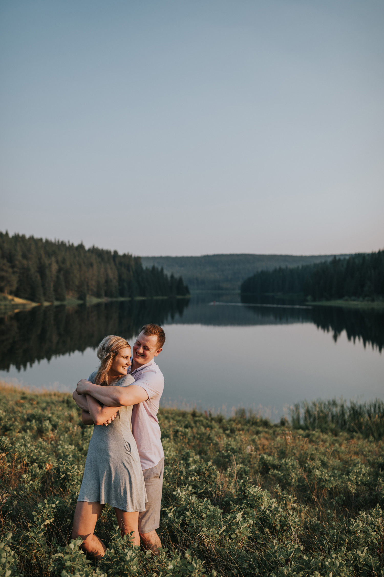 woman looks back at fiancé holding her spruce coulee lake