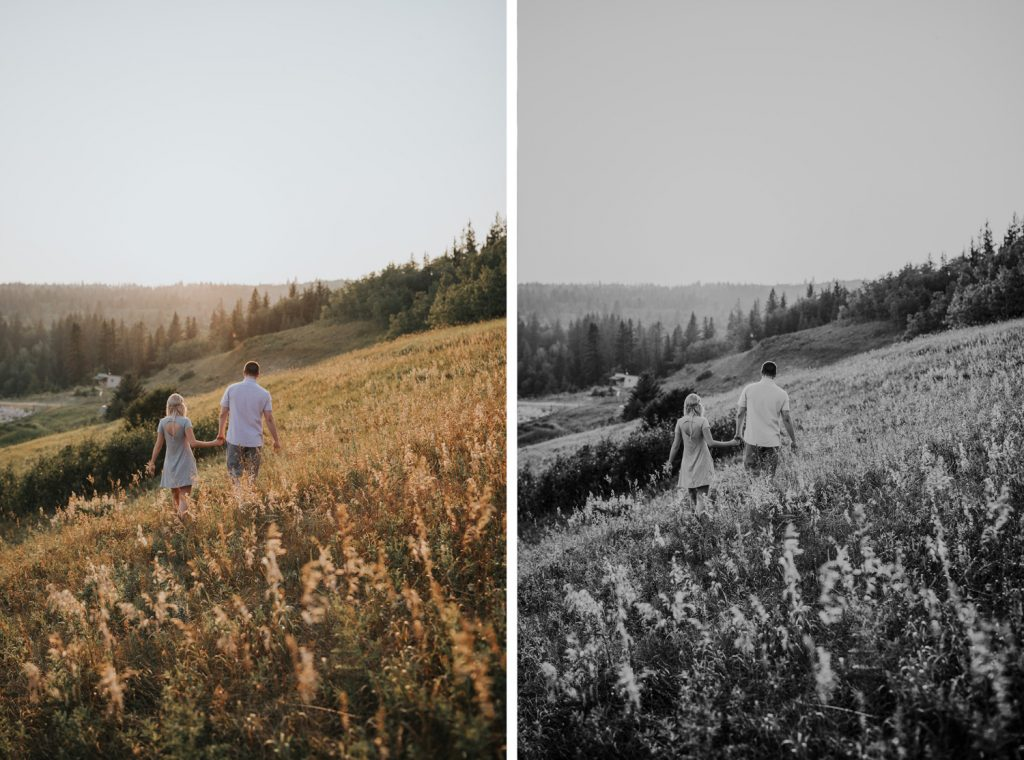 engaged couple walks on hillside into sunset