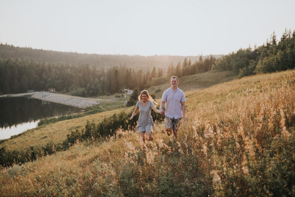 couple laughs running in field at golden hour sunset