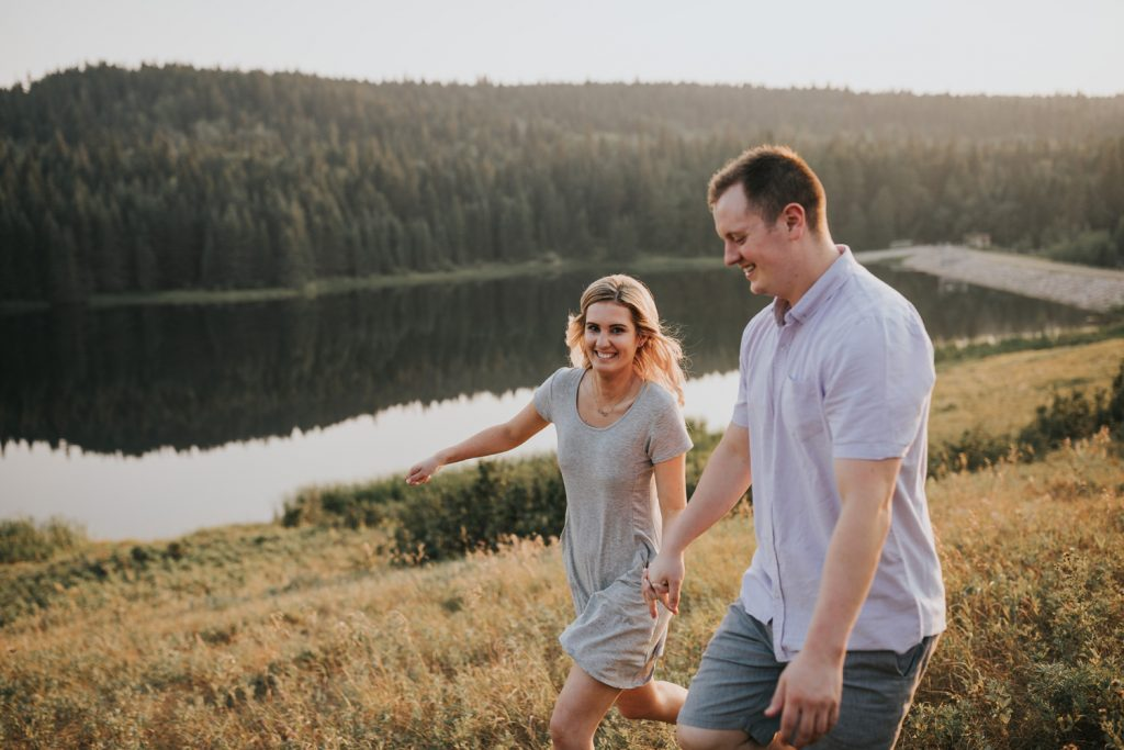 couple smiles while running through the grass at sunset spruce coulee alberta