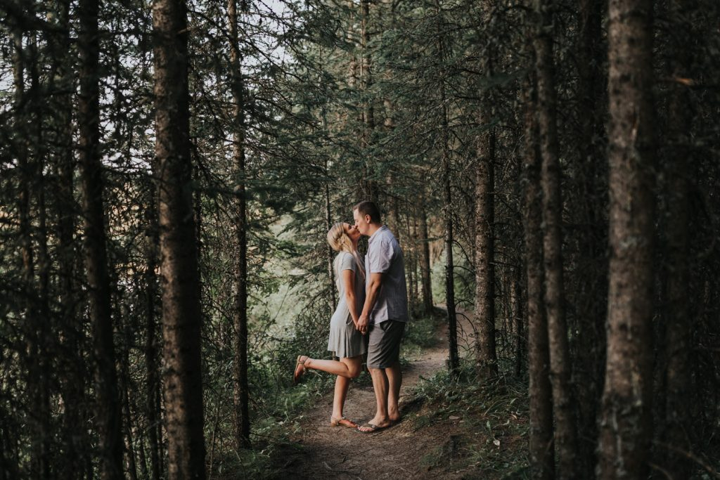 couple leans in for a kiss in spruce coulee forest