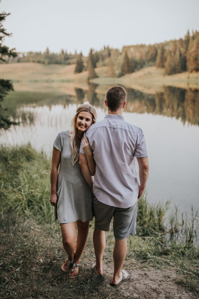 couple stands opposite ways arms linked spruce coulee lake