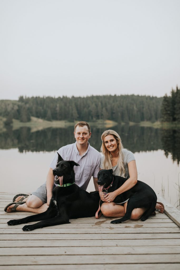 couple sits on dock with two dogs lakeside alberta