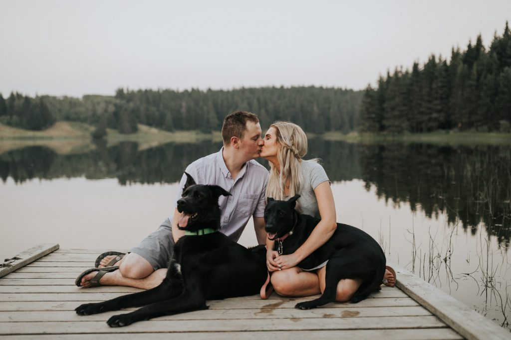 couples kissing on dock with two dogs spruce coulee lake alberta
