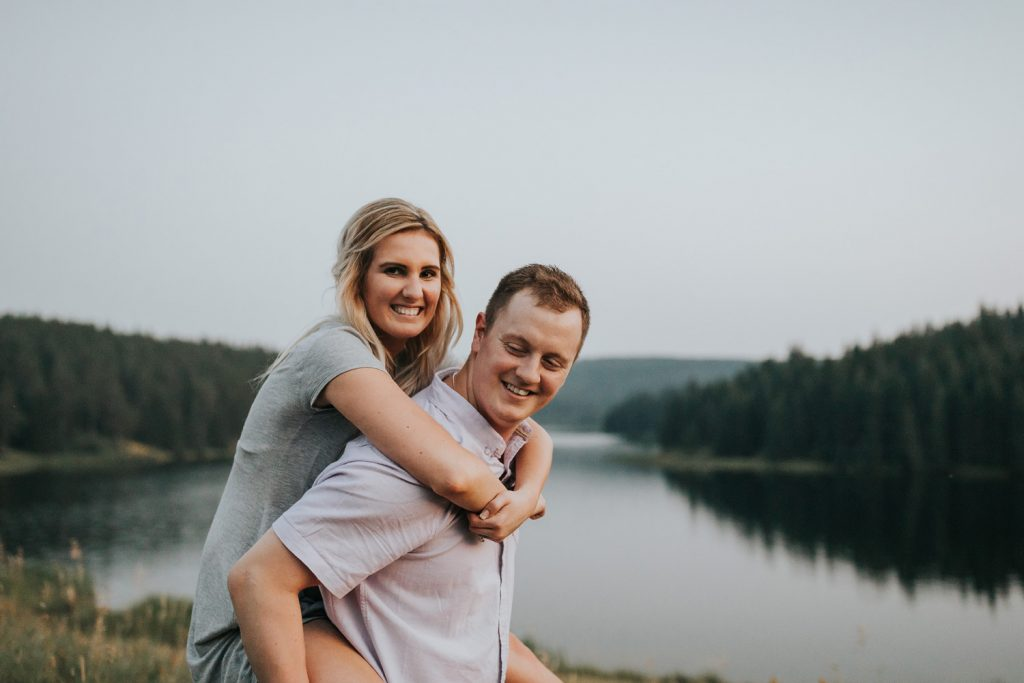 man gives fiancé piggy back ride by lake cypress hills alberta engagement