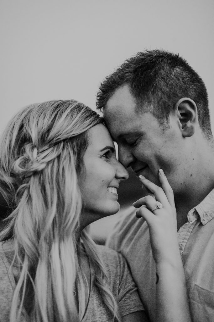 engagement ring photo couple smiles as she touches his cheek