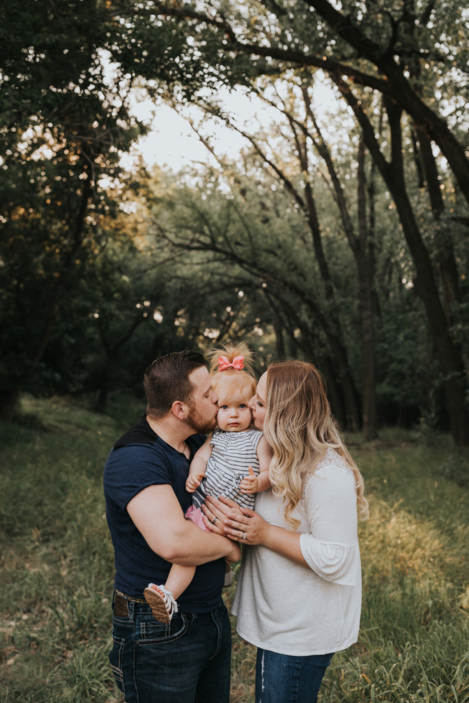 mom and dad kiss toddler on cheeks medicine hat