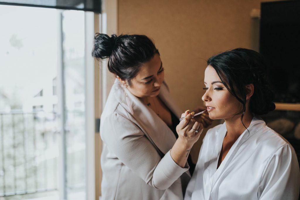 bride having lipstick applied wedding day makeup