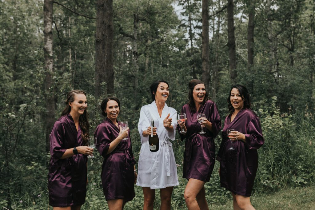 bride laughs with bridesmaids after champagne pop