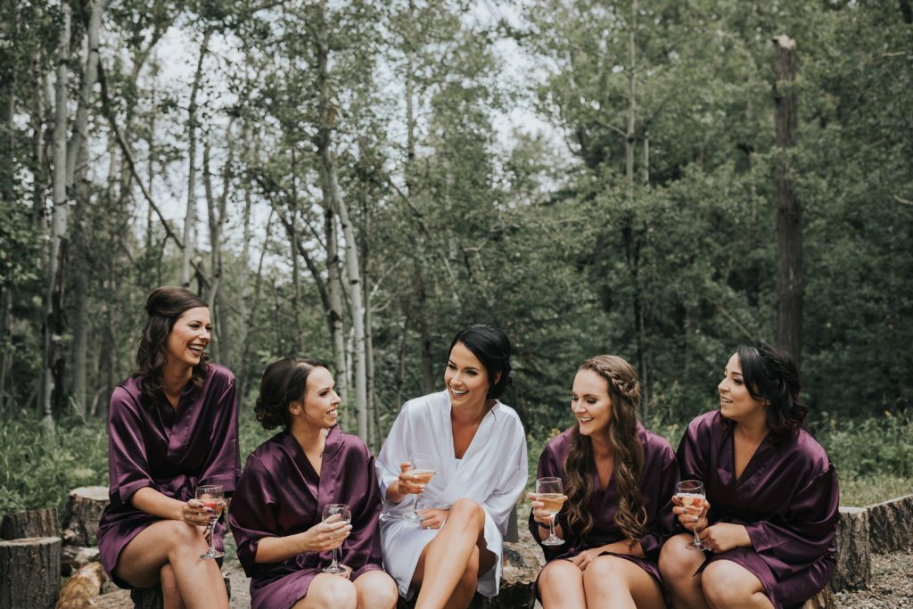 bride and bridesmaids laugh drinking champagne outside