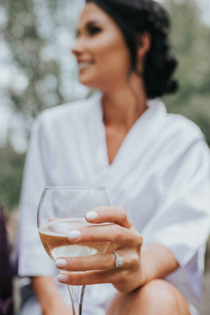 close-ups brides ring holding champagne glasses