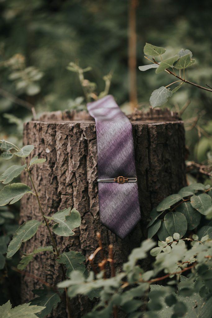 grooms tie and tie clip on tree stump
