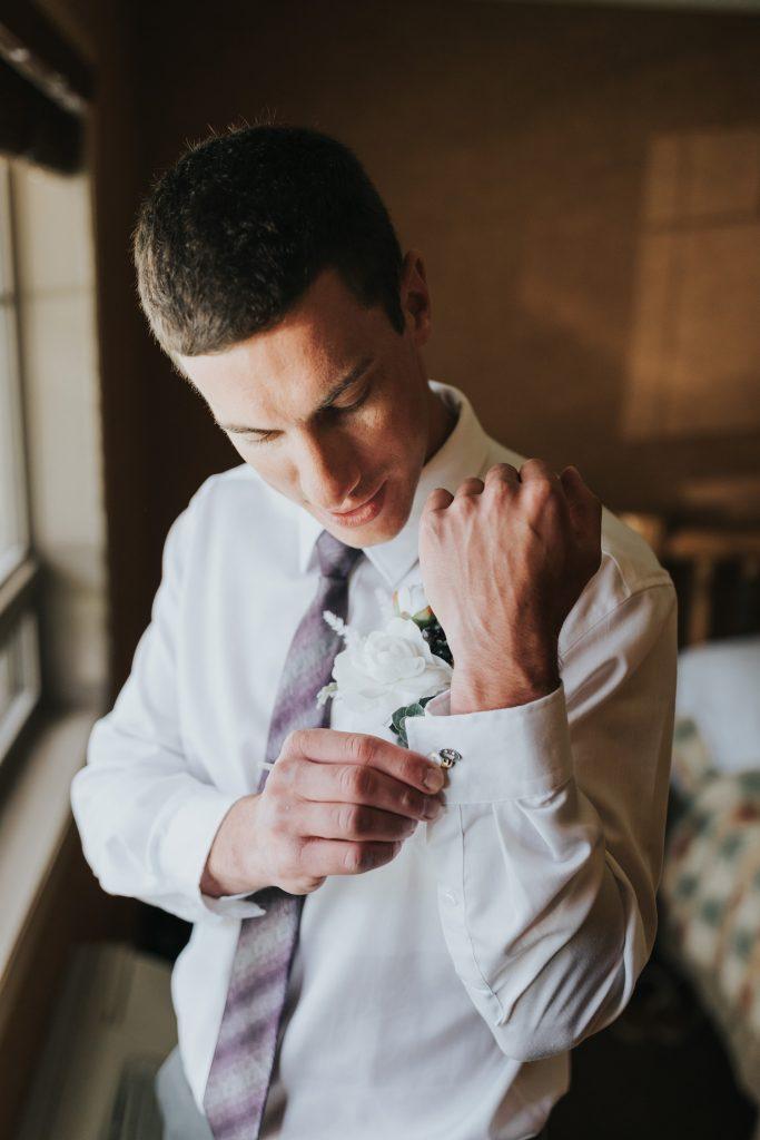 groom putting on cufflinks elkwater lake lodge