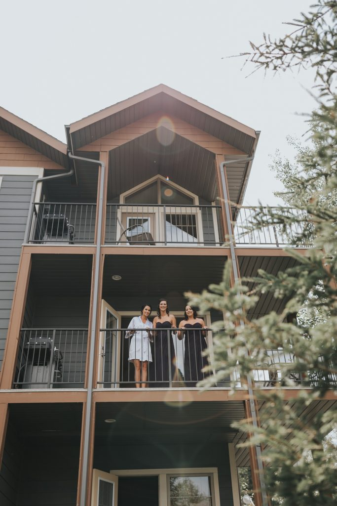 bride and bridesmaids signing and dancing on balcony elkwater lake lodge