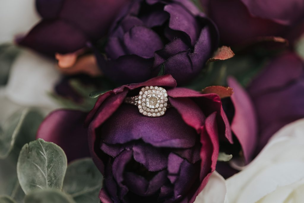 detail photo brides ring with wedding bouquet