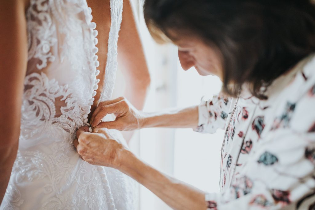 brides mother does up wedding dress buttons