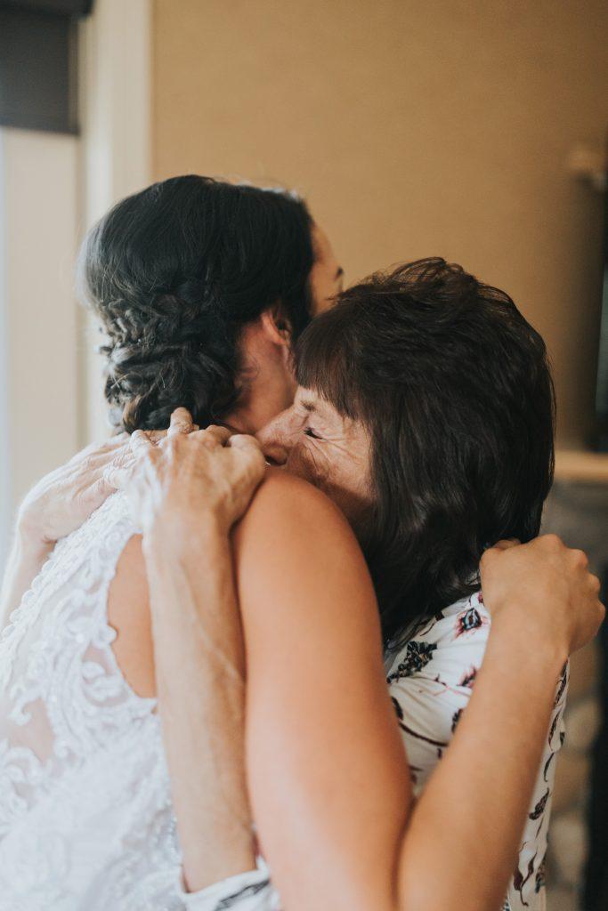 bride hugs her mom after doing up wedding dress