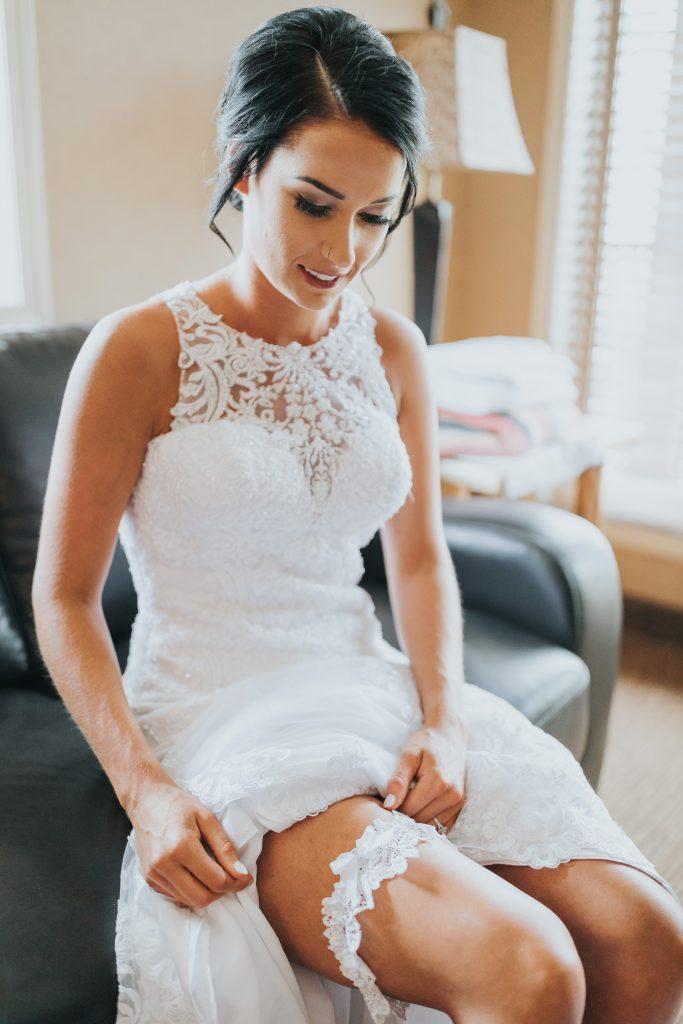 bride puts on her wedding garter
