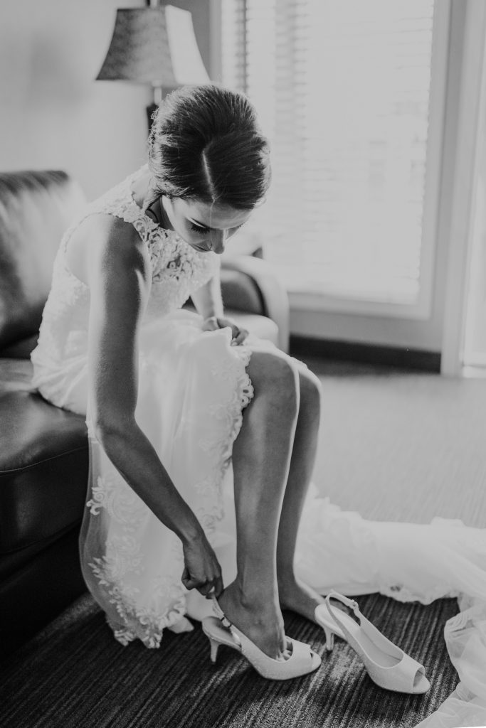 bride puts on her wedding shoes