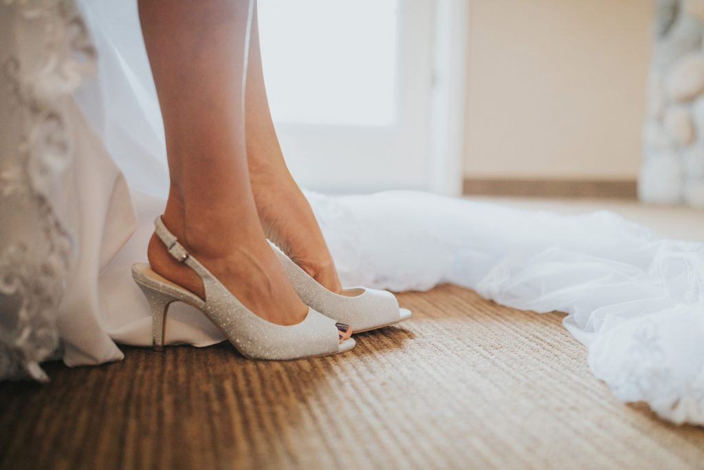 close-up bride putting on wedding shoes sparkly high heels