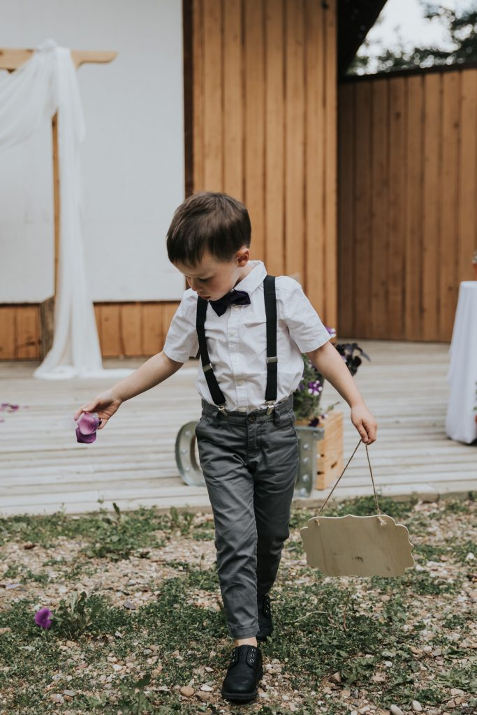 ring bearer throws petals during ceremony