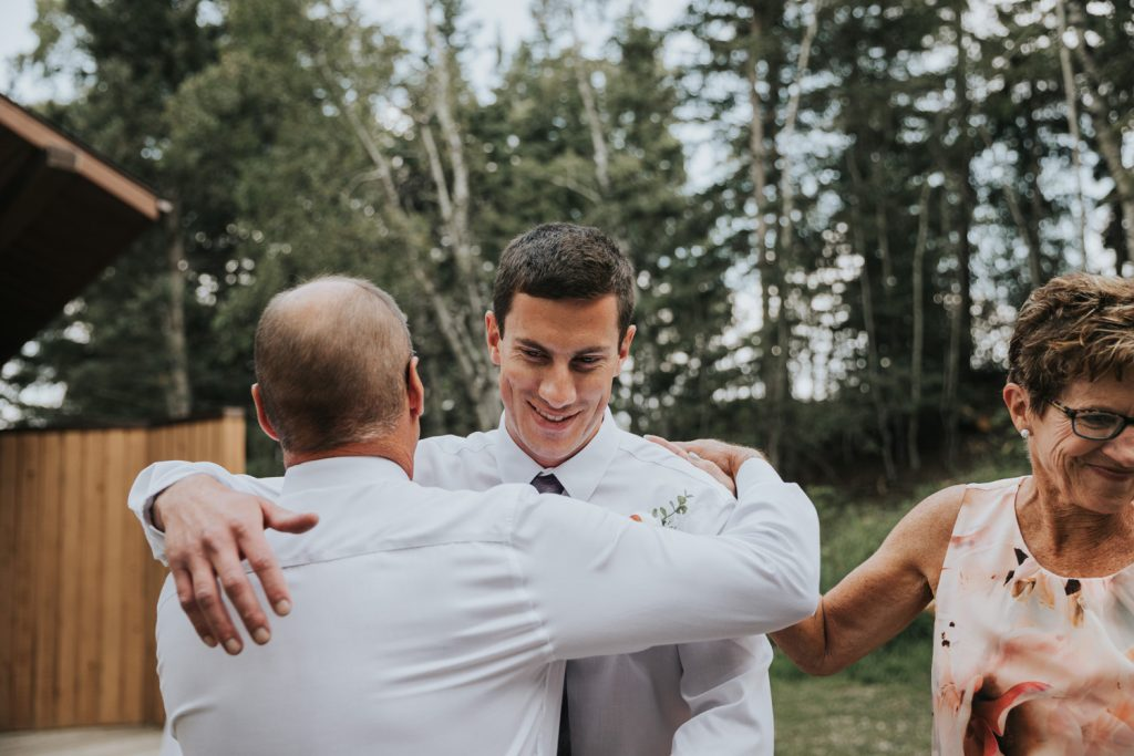 groom hugs parents after walking down aisle wedding ceremony