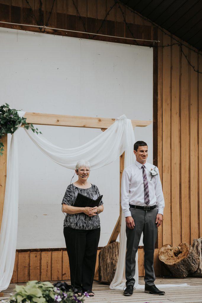 groom smiles as groomsmen walk down aisle