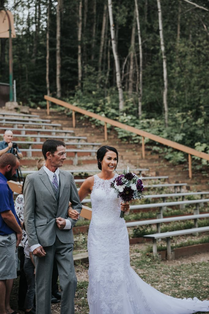 bride smiles at her groom walking with her father