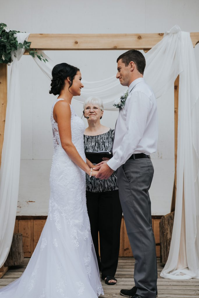 bride and groom smiling during wedding ceremony under arch