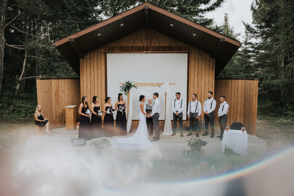 elkwater amphitheatre wedding party photo with rainbow reflection