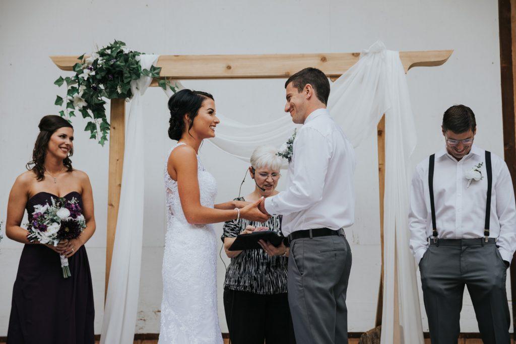 bride smiles during wedding ceremony vows