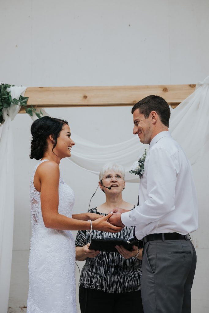 bride and groom laugh as groom puts bride's ring on her finger