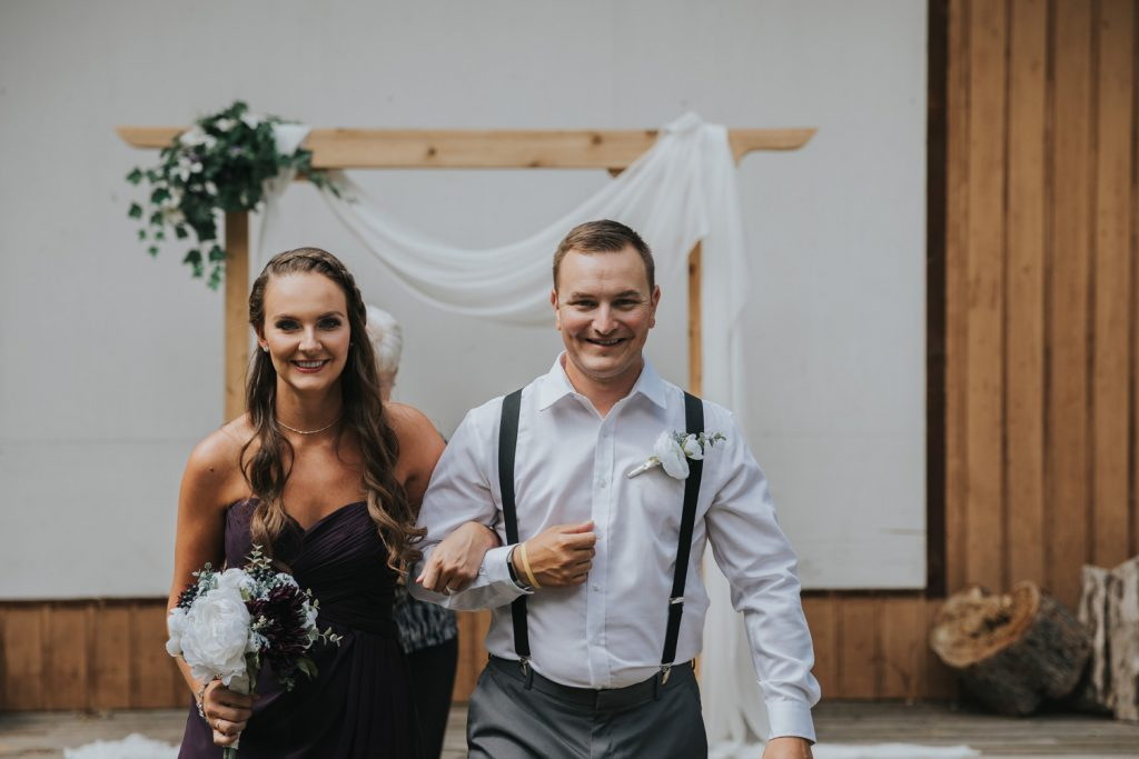 bridesmaid and groomsman walking back down aisle elkwater amphitheater
