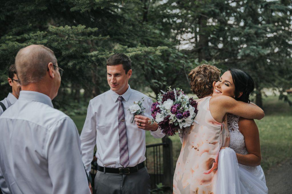 parents hug bride and groom after ceremony