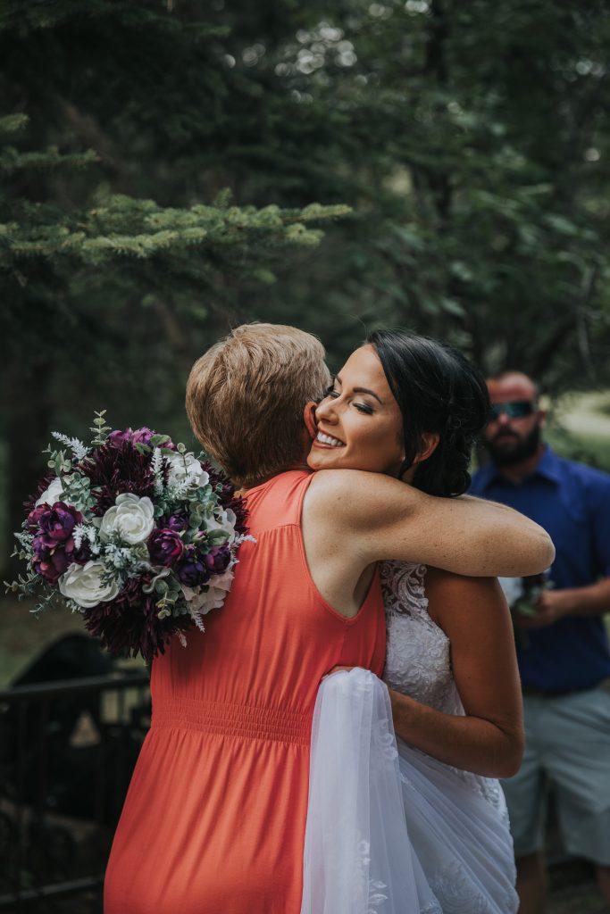 guest hugs bride after ceremony